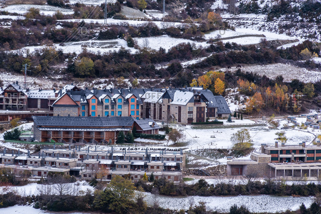 Drone view of cottages and autumn trees located on snowy hill slope in town