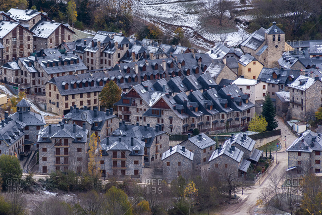 Drone view of houses and autumn trees located on snowy hill slope in town