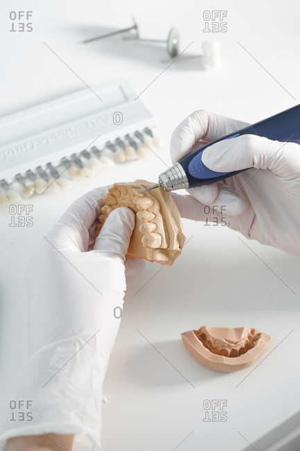 From above of crop anonymous dentist in medical gloves grinding dental prosthesis with professional tool while working in modern laboratory