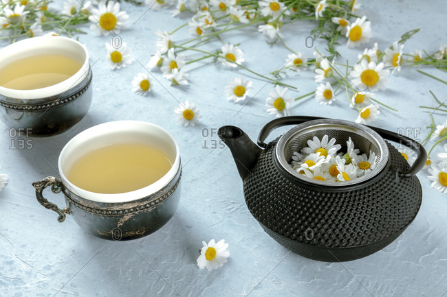 From above pot of chamomile tea served on rustic mug with fresh flowers on blue background