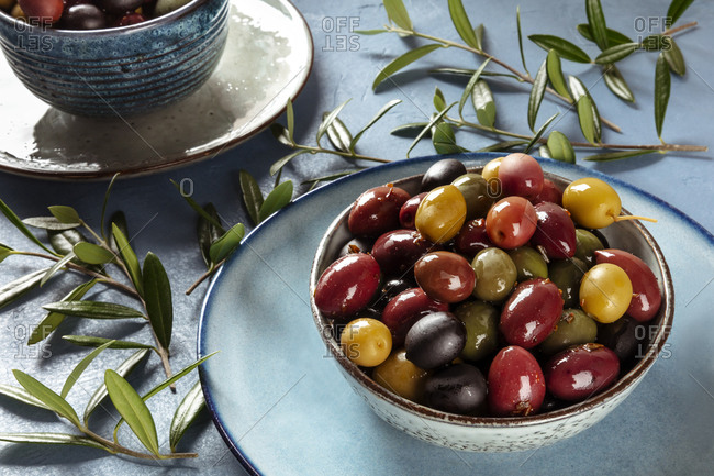 Olives. A variety of green, black and red olives, with leaves