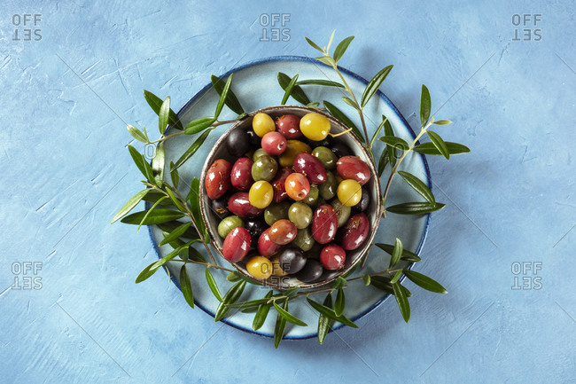 Olives. A variety of green, black and red olives, with leaves, overhead shot