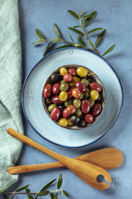 Olives. A variety of green, black and red olives, with leaves and wooden spoons, top-down shot