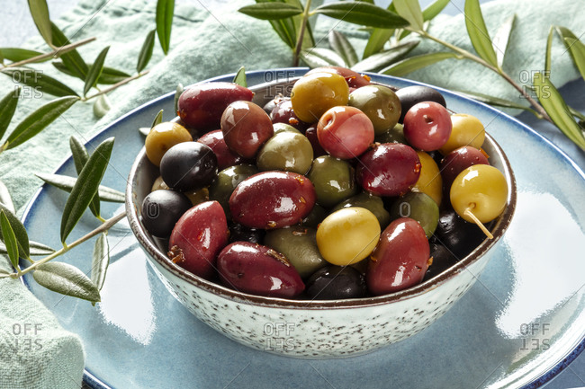 Olives. A variety of green, black and red olives, with leaves, a close-up