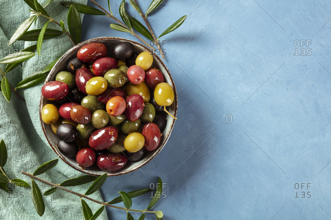 Olives. A variety of green, black and red olives, with leaves, shot from the top with a place for text