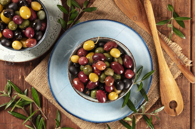 Olives. A variety of green, black and red olives, with leaves, shot from the top on a rustic wooden background