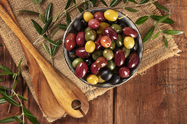 Olives. A variety of green, black and red olives, with leaves, shot from above on a rustic wooden background with a place for text