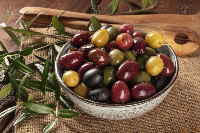 Olives. A variety of green, black and red olives, a close-up with leaves on a rustic wooden background