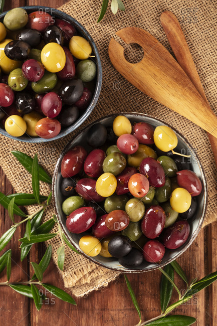 Olives. A variety of green, black and red olives, with leaves on a rustic wooden background, shot from the top