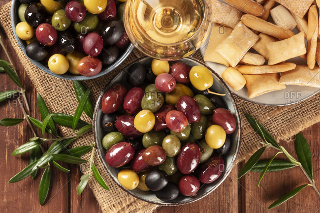 Olives. A variety of green, black and red olives, with wine and breadsticks on a rustic wooden background, overhead close-up shot