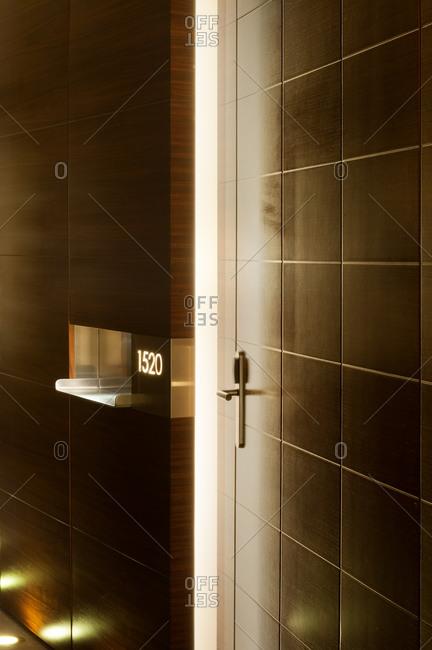 Simple door of room in illuminated hallway in hotel designed in minimalist style