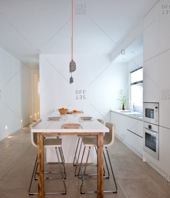 Interior of contemporary kitchen in Scandinavian style with dining table and bar stools