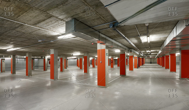 Modern parking lot with yellow stone columns and concrete floor located underground