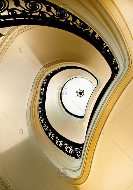 From below white elegant spiral stairway with black ornamental banister located inside classic building