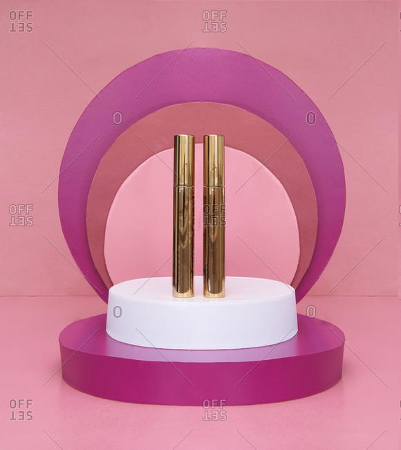Mascara brush over set of golden tubes arranged on pink background