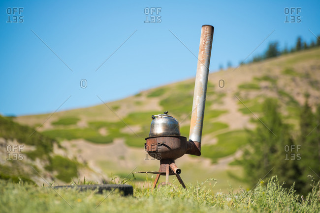 Rusty wood stove with metal kettle placed on background of picturesque landscape with grassy terrain and blue sky