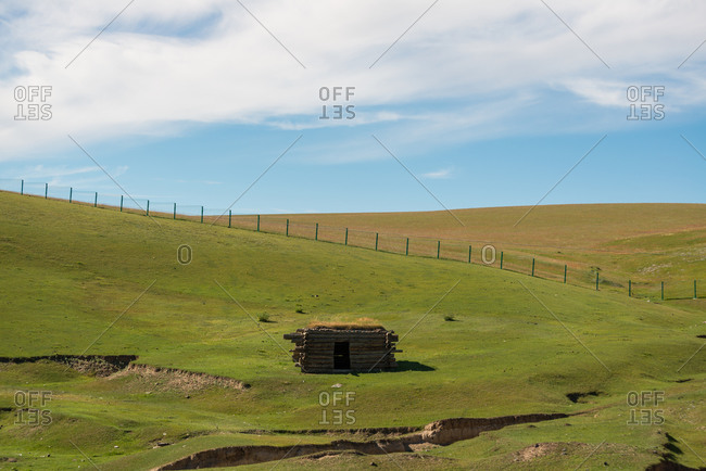 Small cabin located on grassy slope and surrounded by fence on sunny day in countryside