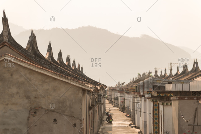 Narrow pathway surrounded by traditional stone buildings with ornamental roofs in Daimei Village during sunrise