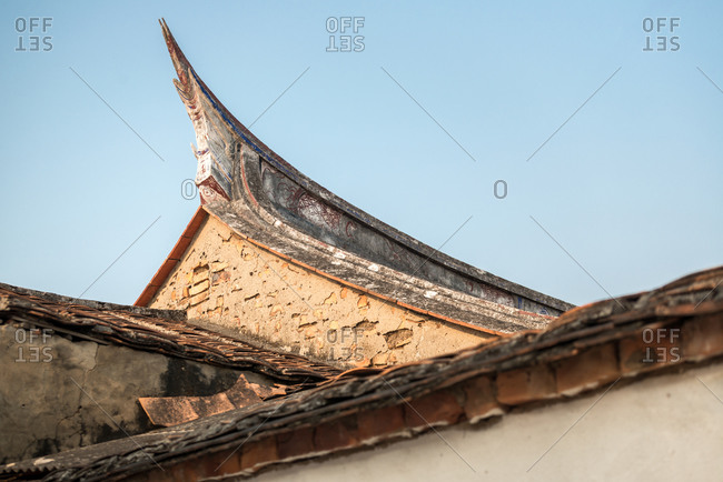 From below of aged stone houses with decorated roofs on background of cloudy sky in Daimei Village