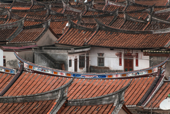 Aerial view of aged oriental buildings with curved roofs covered with tile and placed in rows in Daimei Village