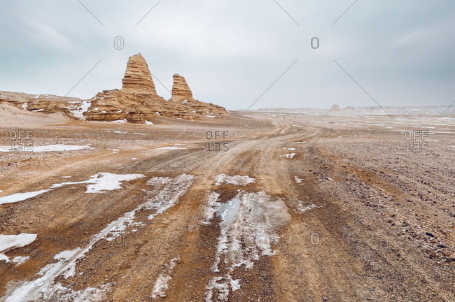Lonely old stone building located amidst desert snowy terrain under cloudy sky with bright sun