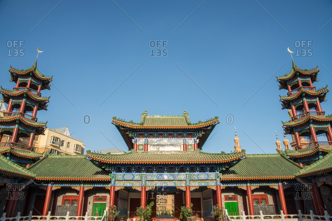 Low angle of exterior of oriental building with curved roof and ornamental pagodas on background of cloudless sky