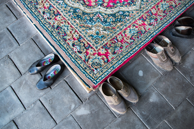 August 3, 2015: From above of colorful carpet and old footwear placed on stone floor in Muslim church