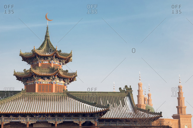 Exterior of oriental building with curved roof and ornamental pagodas on background of cloudless sky