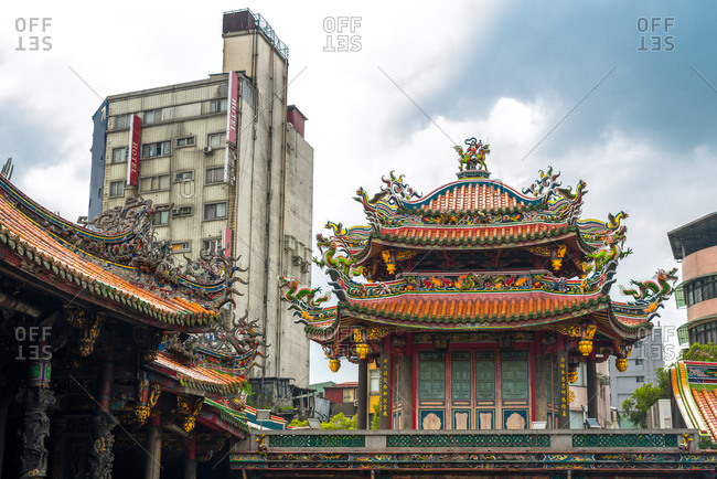 August 16, 2016: Low angle of traditional Bangka Lungshan Temple with ornamental design located near modern city building against cloudy sky in Taiwan