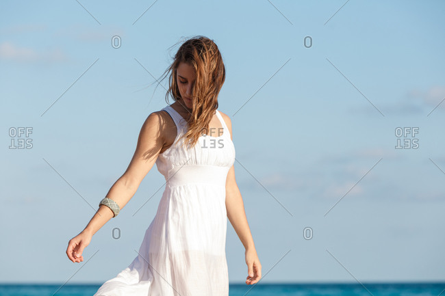 Serene female wearing white summer dress standing on background of turquoise water of sea and enjoying sunny weather on beach during vacation