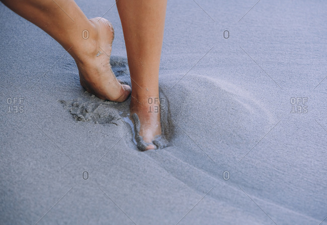 Unrecognizable carefree female with slim legs walking barefoot on sand at seashore while enjoying summer holiday