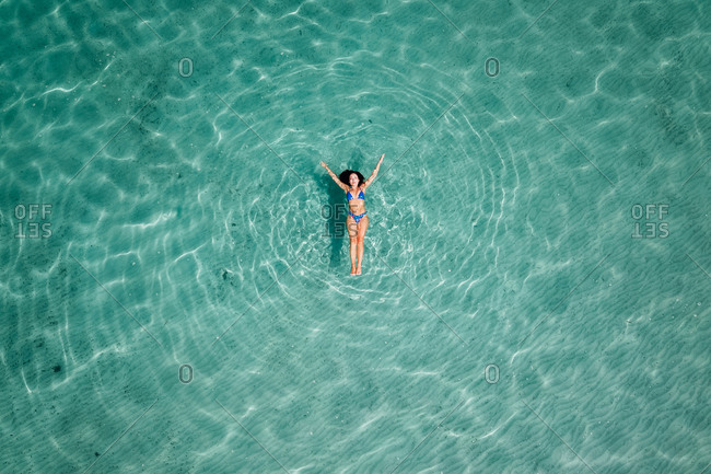 Drone view of relaxed female in bikini floating on clear water surface and relaxing during summer vacation
