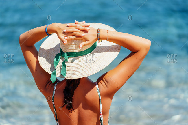 Back view of relaxed female tourist in straw hat and bikini standing on background of majestic seascape and admiring sea during summer holiday