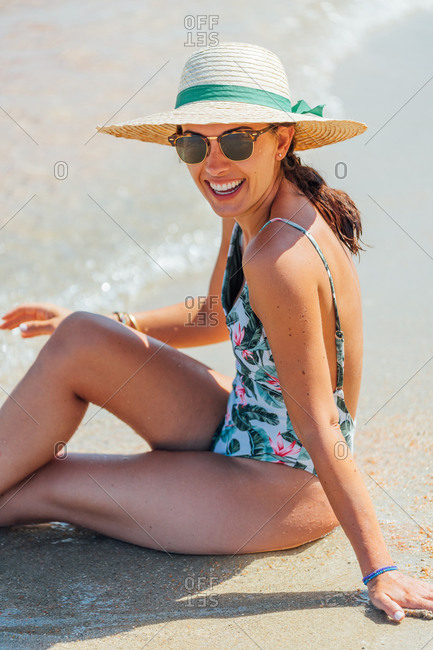 Smiling female tourist in straw hat and swimsuit full-length while chilling at seaside during summer holiday