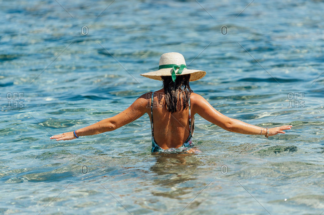 From above back view of female traveler in bikini walking in clean water of sea while enjoying summer holiday
