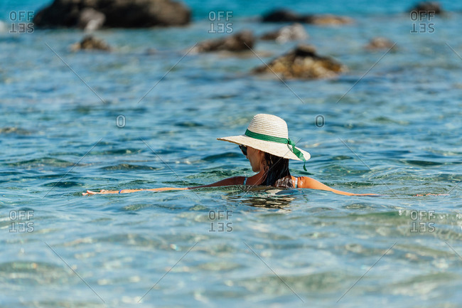 Back view of female tourist wearing straw hat and swimsuit standing in clear water of sea and enjoying vacation on sunny day