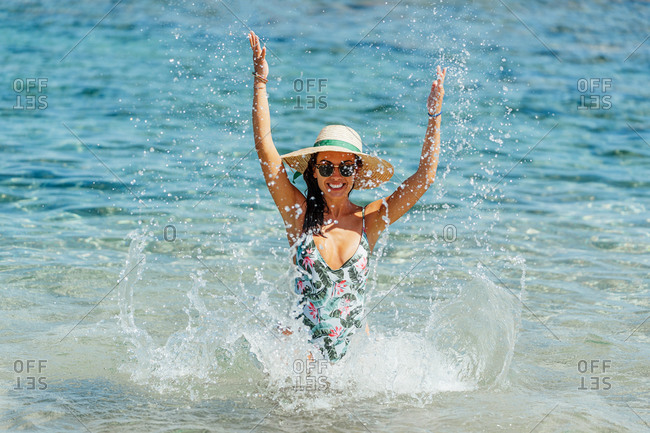 Cheerful female tourist in swimsuit and straw hat standing in clear water of sea and having fun while looking at camera and making splashes