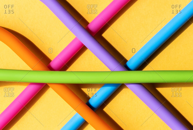 Top view of multicolored reusable straws placed on table in geometric shape demonstrating eco friendly concept