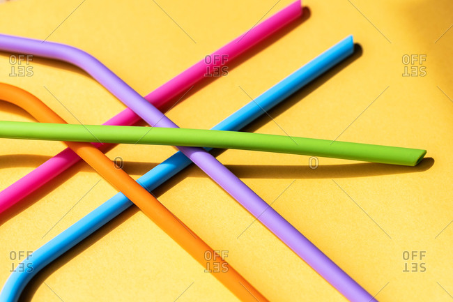 Top view of heap of recyclable silicone straws arranged on yellow background showing zero waste concept