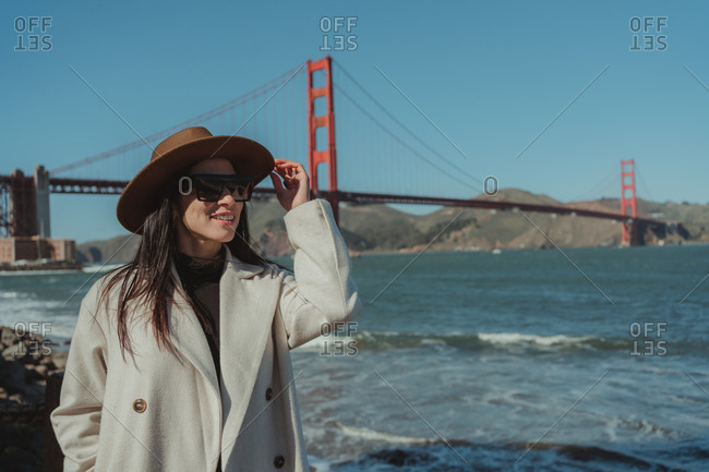 Side view of smiling young woman in trendy outfit with hat and sunglasses standing on embankment against Golden Gate Bridge in California in sunny day
