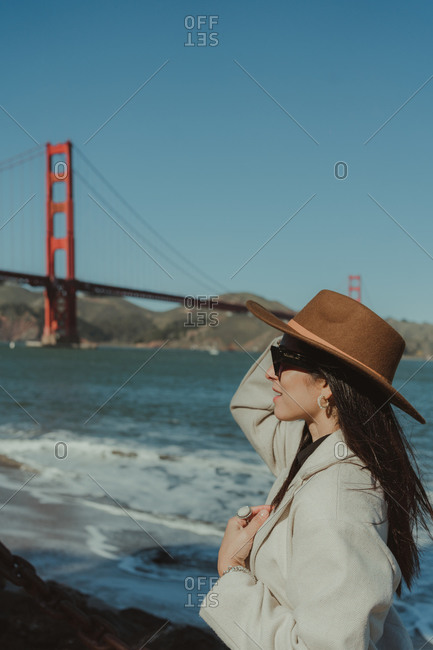 Side view of smiling young lady in trendy outfit with hat and sunglasses standing on embankment against Golden Gate Bridge in California in sunny day