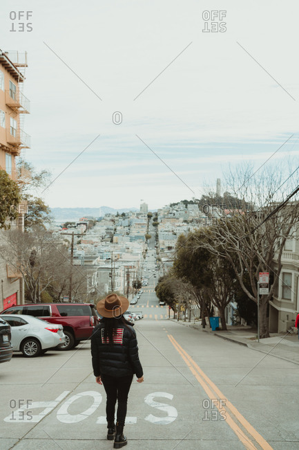 Back view of unrecognizable female traveler in trendy outfit and hat standing near stop sign on roadway leading towards hill during stroll and sightseeing in San Francisco city in cloudy day