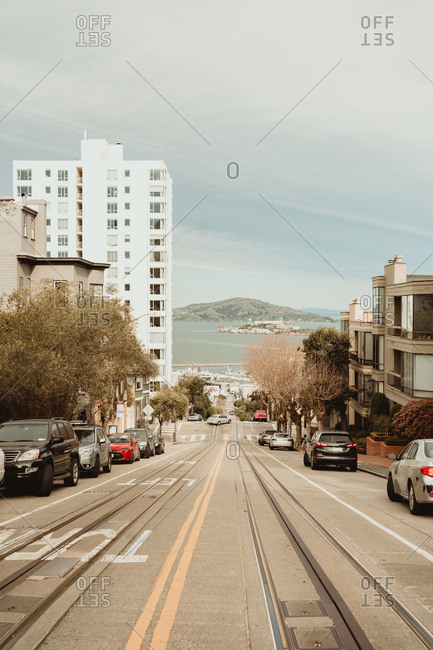 Perspective view of straight paved roadway with railway going down in San Francisco city district