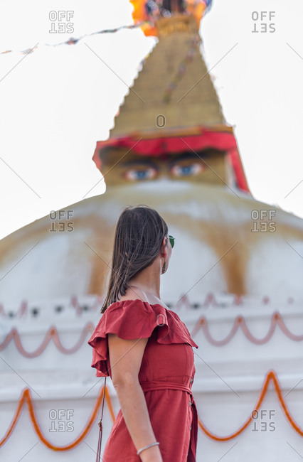 Side view of woman standing near Buddhist temple with decorative garlands and tower under cloudy sky in daylight