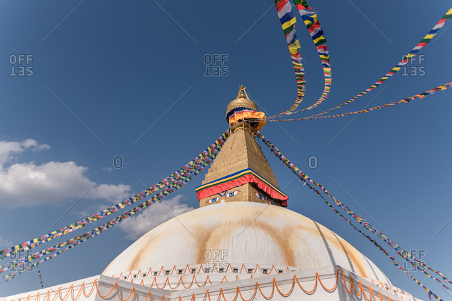 Low angle of old Buddhist hemispherical monument with ornament and decorative eyes on tower with small cupola and garlands on top under sky in afternoon