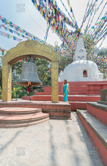 Female tourist in dress looking away while standing on pavement close to old stone hemispherical stupa with cupola on top under garland with flags and big bell in summer