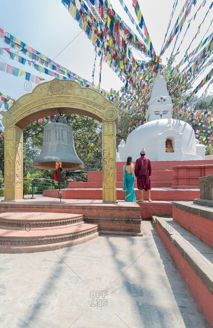 Back view of unrecognizable couple holding hands while standing on red stairs looking at ancient sculpture and arch with big bell under garland with prayer flags