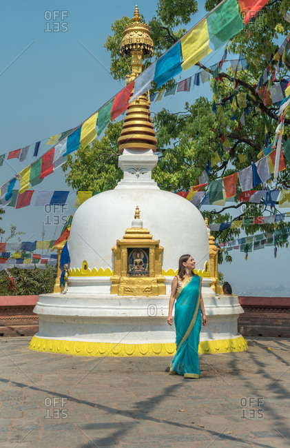 Female tourist in dress looking away while standing on pavement close to old stone hemispherical stupa with cupola on top under garland with flags in summer
