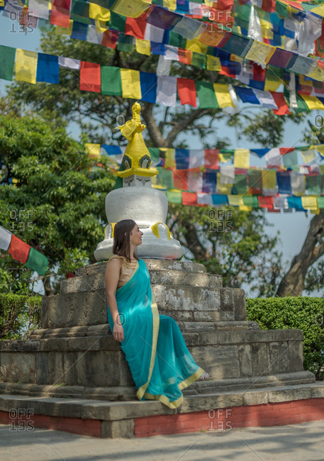 Female tourist in dress looking away while sitting on old stone on a Buddhist stupa with cupola on top under garland with flags in summer