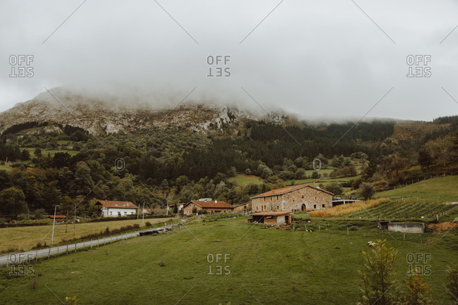 Green meadow with old buildings near trees on mount with mist on peak under cloudy sky in summer in countryside